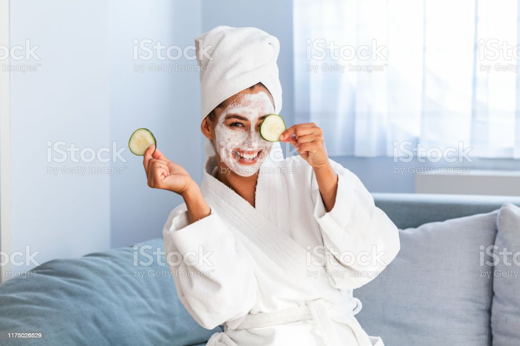 Jonge vrouw met reinigende masker op haar gezicht thuis. Huidverzorging. Vrouw apliggend Beauty Mask, close-up. Zo mooi. Close-up van meisje met Beauty Mask op haar gezicht op zoek in spiegel. - Royalty-free Aanbrengen Stockfoto
