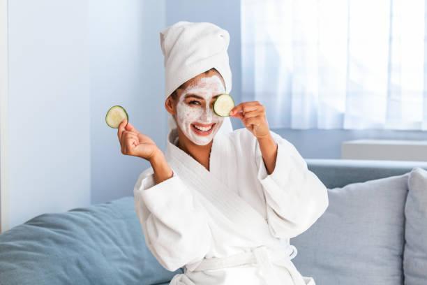 jonge vrouw met reinigende masker op haar gezicht thuis. huidverzorging. vrouw apliggend beauty mask, close-up. zo mooi. close-up van meisje met beauty mask op haar gezicht op zoek in spiegel. - mirror mask stockfoto's en -beelden