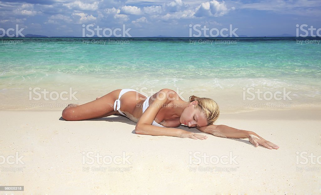 young woman with closed eyes resting on the beach royalty-free stock photo