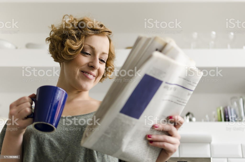 Young woman with coffee and newspaper stock photo