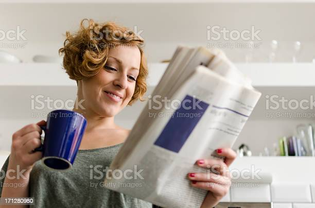 Young Woman With Coffee And Newspaper Stock Photo - Download Image Now