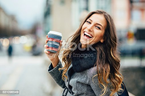 531098549 istock photo Young woman with coffee cup smiling outdoors 531098549