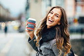 Young woman with coffee cup smiling outdoors