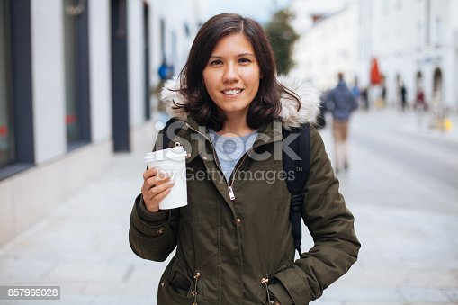 531098549 istock photo Young woman with coffee cup smiling outdoors 857969028