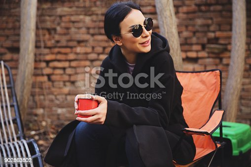 531098549 istock photo Young woman with coffee cup smiling outdoors 902863802