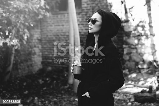 531098549 istock photo Young woman with coffee cup smiling outdoors 902863808