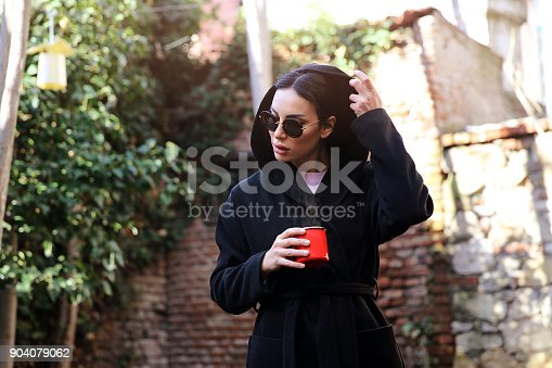 531098549istockphoto Young woman with coffee cup smiling outdoors 904079062