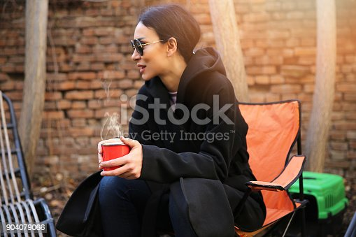 531098549 istock photo Young woman with coffee cup smiling outdoors 904079066