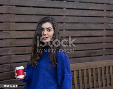 531098549istockphoto Young woman with coffee cup smiling 1152613233