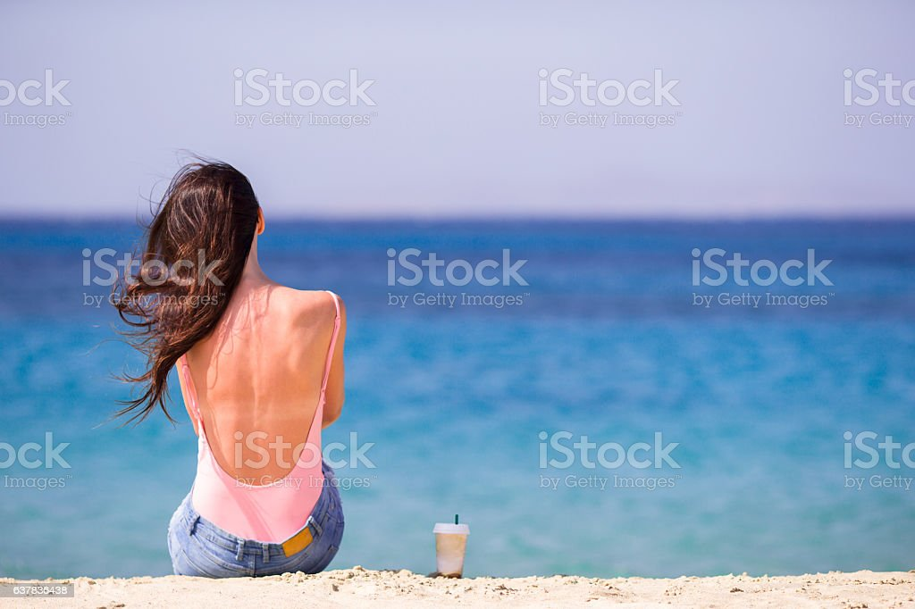 Young woman with coffee on the beach during tropical vacation. stock photo