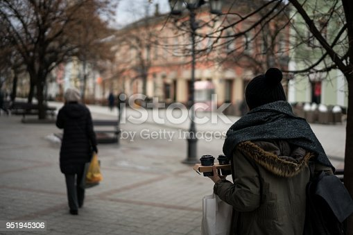 531098549 istock photo Young woman with coffee smiling outdoors 951945306