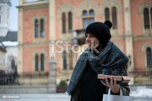 531098549istockphoto Young woman with coffee smiling outdoors 951946536