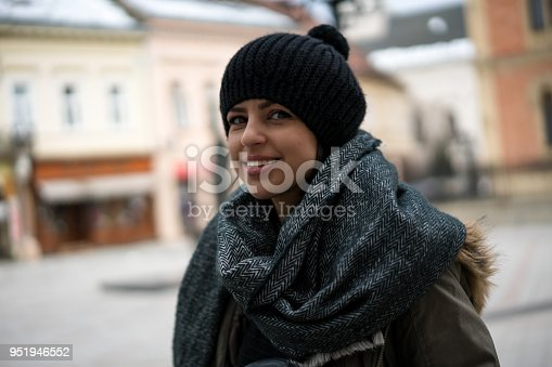 531098549 istock photo Young woman with coffee smiling outdoors 951946552