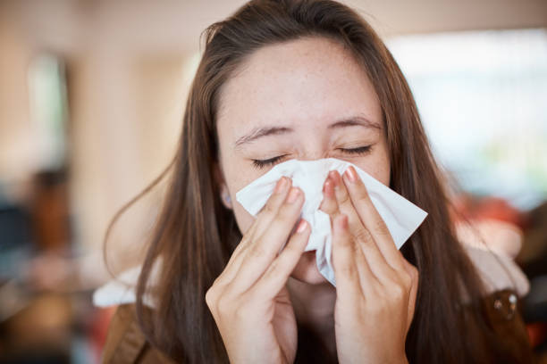 Young woman with cold or flu blows her nose on a tissue Young woman has a respiratory infection. mucus stock pictures, royalty-free photos & images