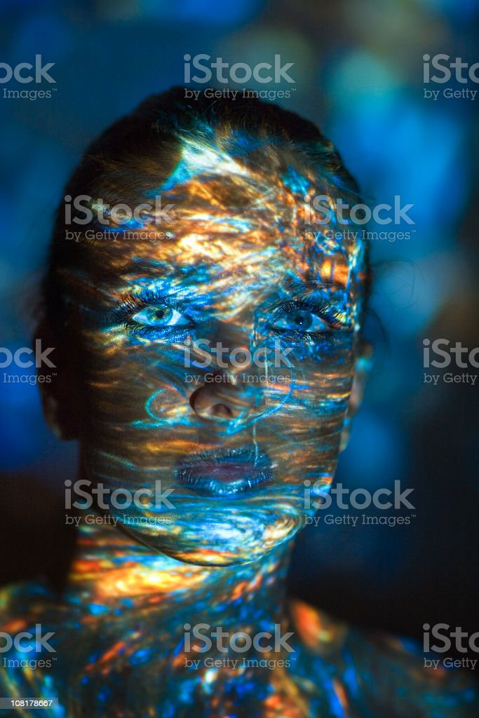 Young Woman with Colored Light Shadows All Over Face stock photo