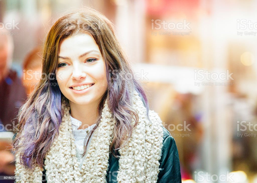 Young woman with colorful hair smiling as she walks down the street...