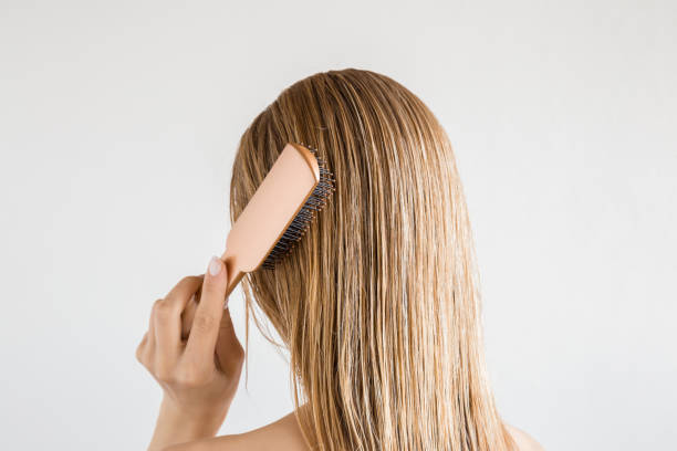 Young woman with comb brushing her wet, blonde, perfect hair after shower on the gray background. Care about beautiful, healthy and clean hair. Beauty salon concept. Back view. stock photo