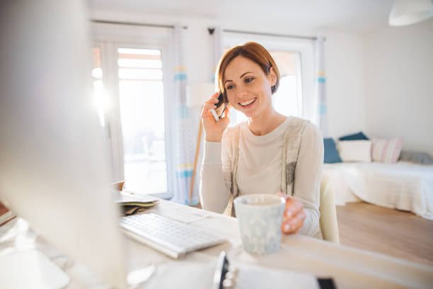 A young woman with computer and smartphone indoors, working in a home office. stock photo