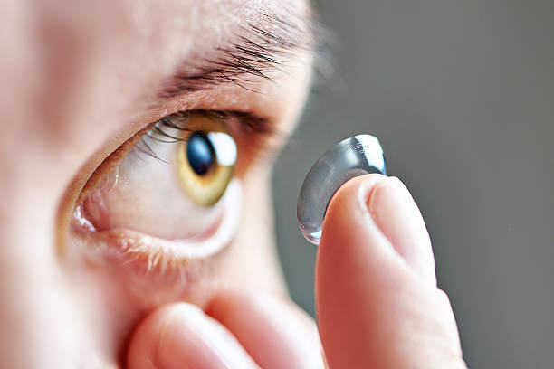 young woman with contact lens - lens eye stock pictures, royalty-free photos & images