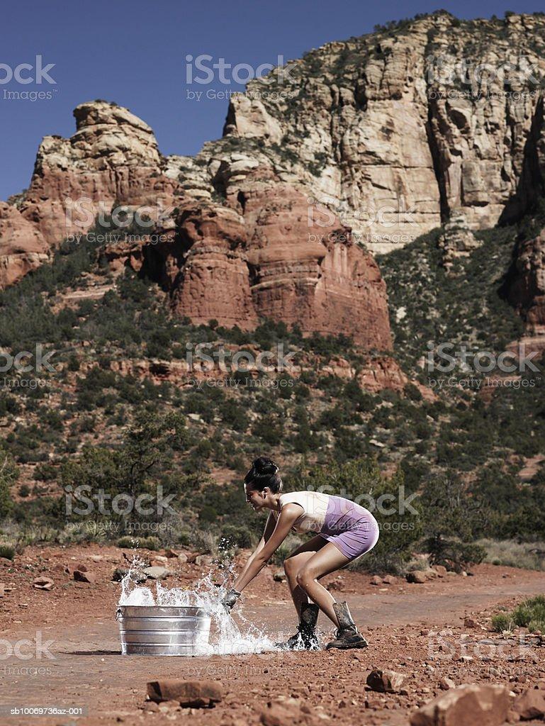 Jovem mulher com recipiente no deserto, vista lateral foto de stock royalty-free