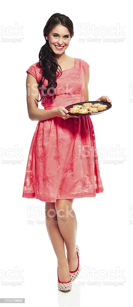 Young woman with cookies Full lenght portrait of cheerful woman holding a tray with cookies and smiling at the camera. 20-24 Years Stock Photo
