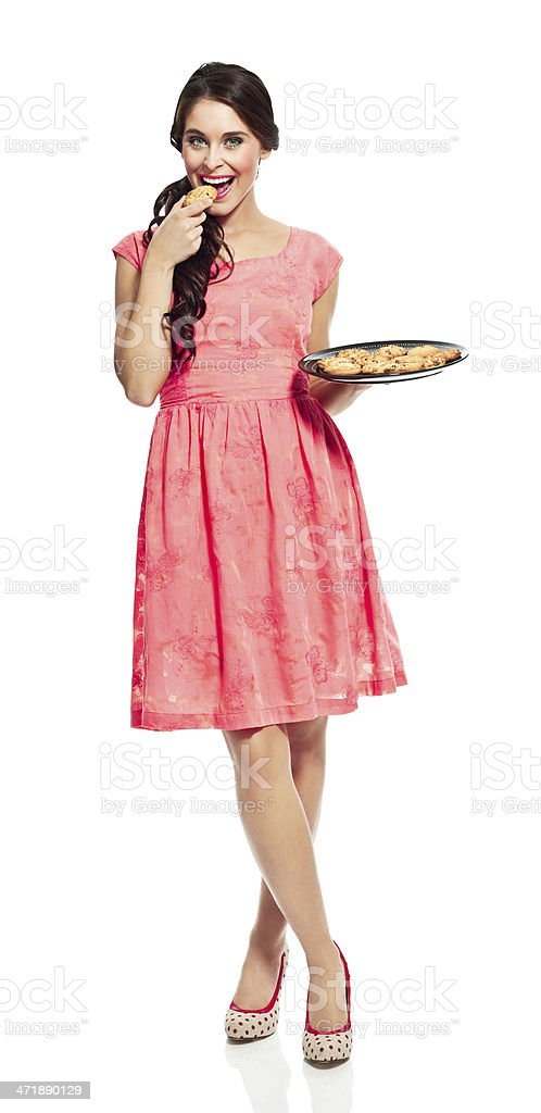Young woman with cookies Full lenght portrait of cheerful woman holding a tray with cookies, eating one of them and smiling at the camera. 20-24 Years Stock Photo