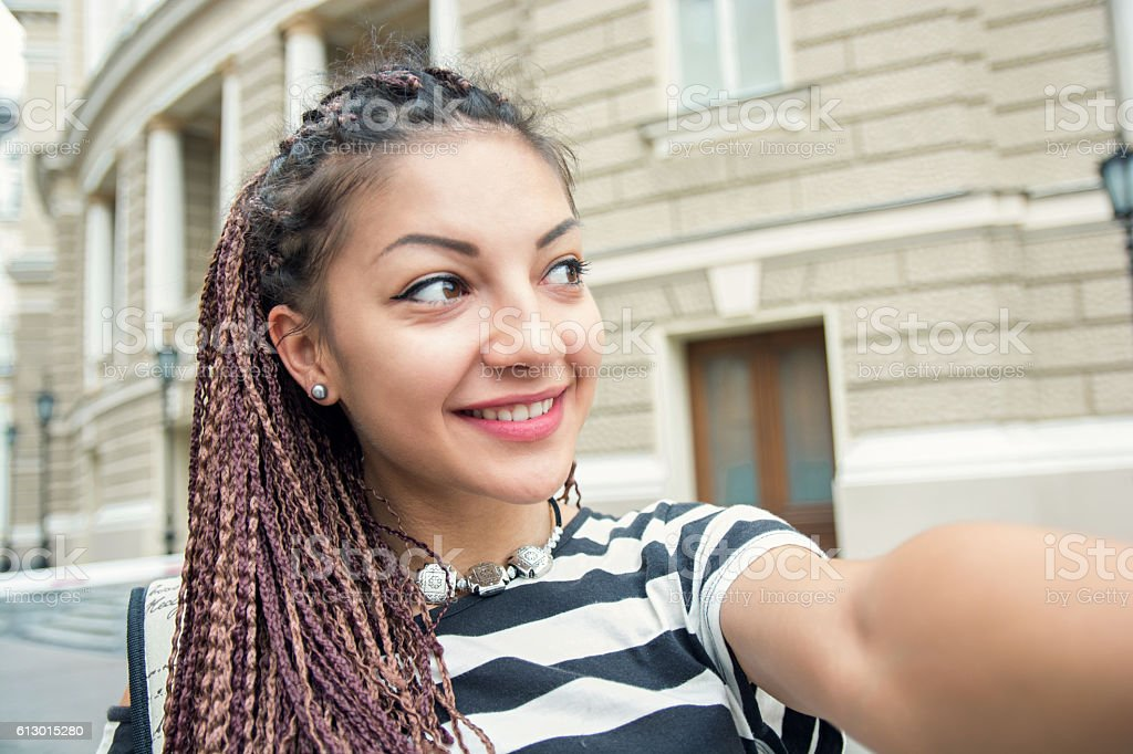 young woman with cornrows making selfie at town stock photo