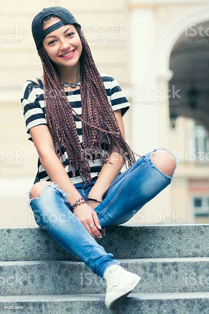 young woman with cornrows sitting on the chairs outdoors stock photo