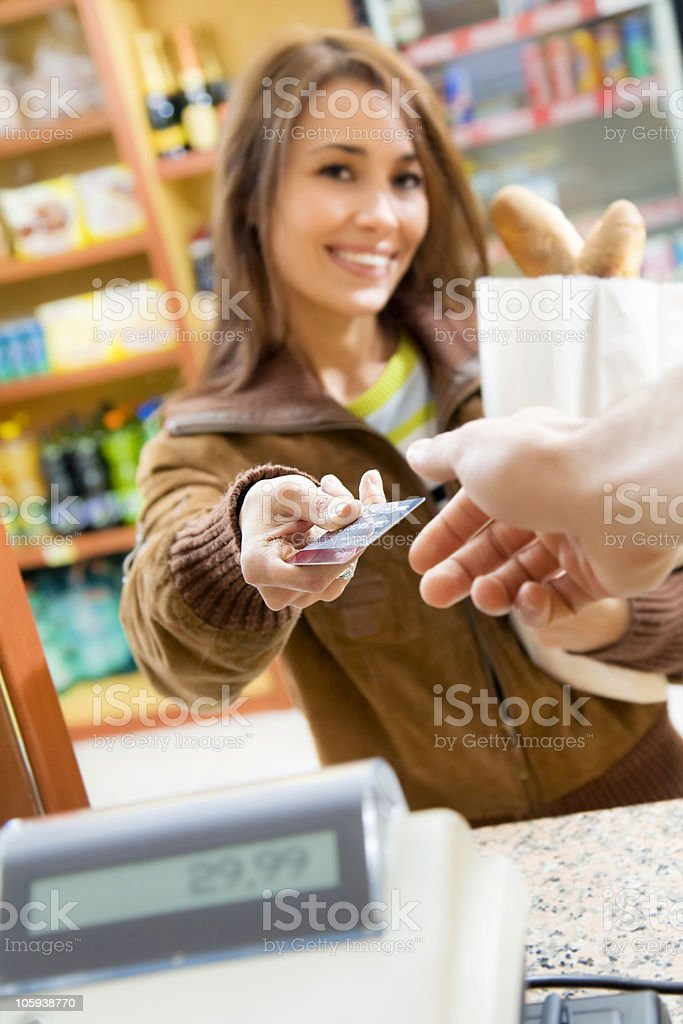 Young woman with credit card in grocery store royalty-free stock photo