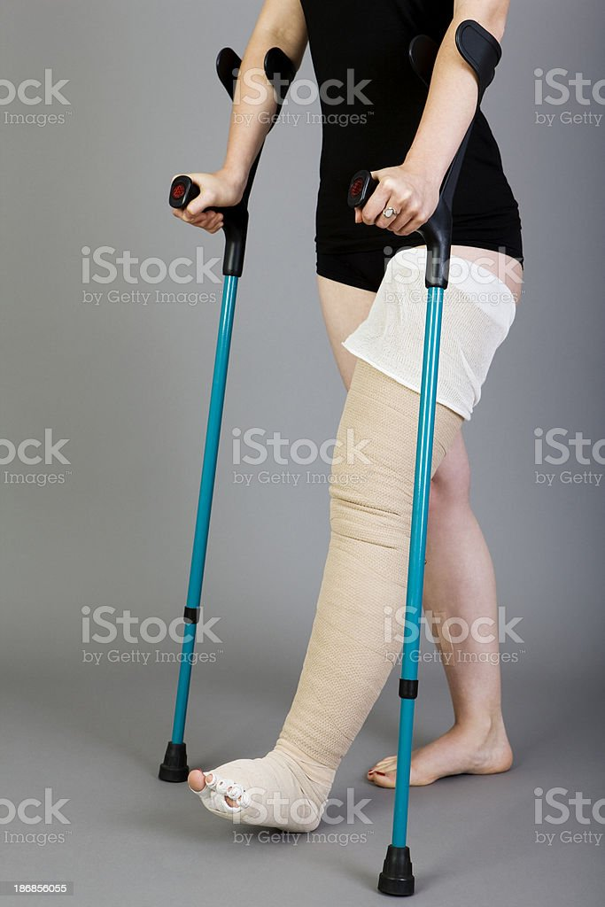 young woman with crutches stock photo