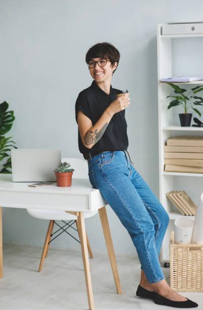 junge frau mit tasse kaffee steht neben dem tisch im büro - kaffeetasse tattoo stock-fotos und bilder