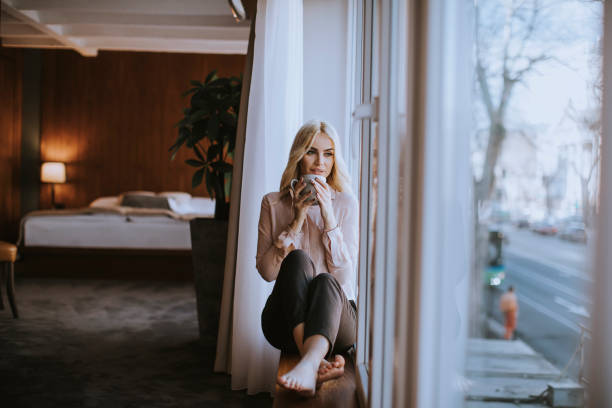 Young woman with cup of tea or coffee sitting and drinking on the window sill at home stock photo