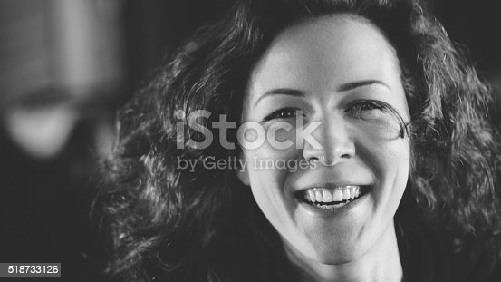 black and white portrait, young woman with curly hair is smiling and laughing