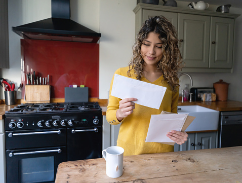 Young woman with curly hair drinking tea and checking her mail at home