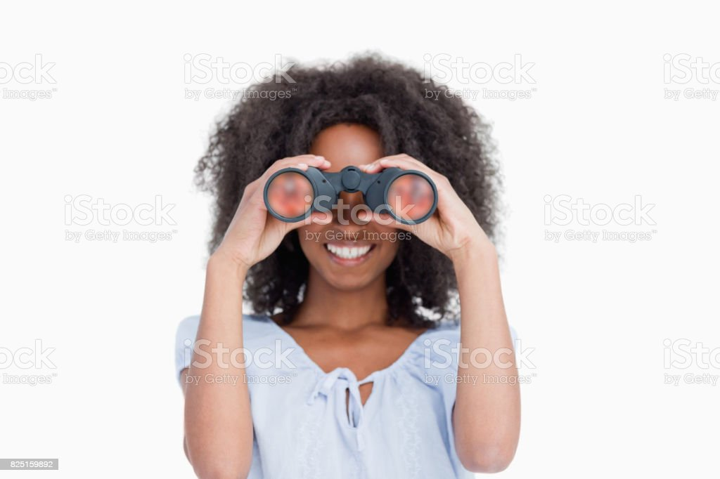 Young woman with curly hair looking through binoculars stock photo