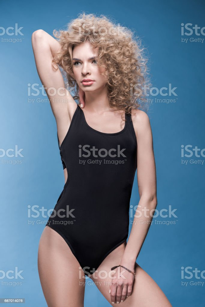 young woman with curly hair posing and looking away Lizenzfreies stock-foto