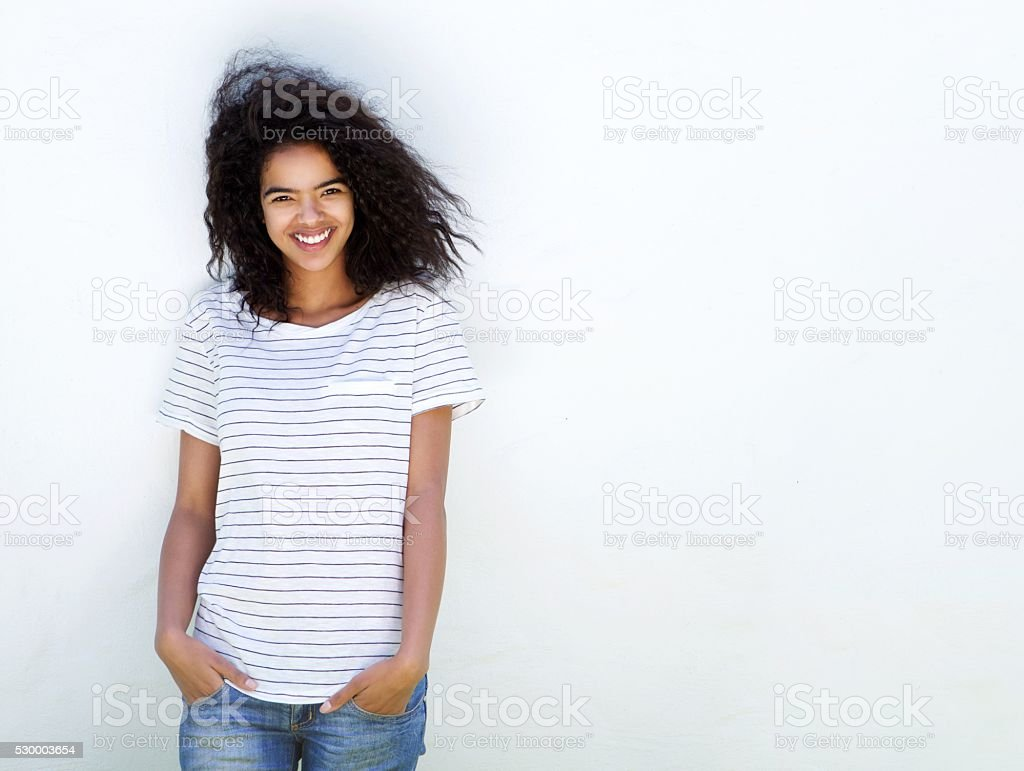 Young woman with curly hair smiling against white background stock photo