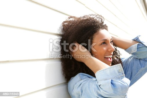 istock Young woman with curly hair smiling 486415343