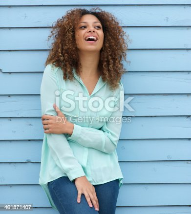 186534921 istock photo Young woman with curly hair standing outdoors and laughing 461871407