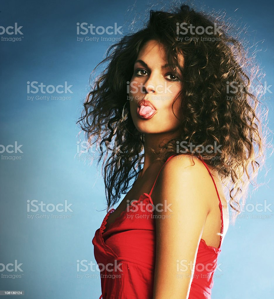 Young Woman With Curly Hair Sticking Tongue Out royalty-free stock photo