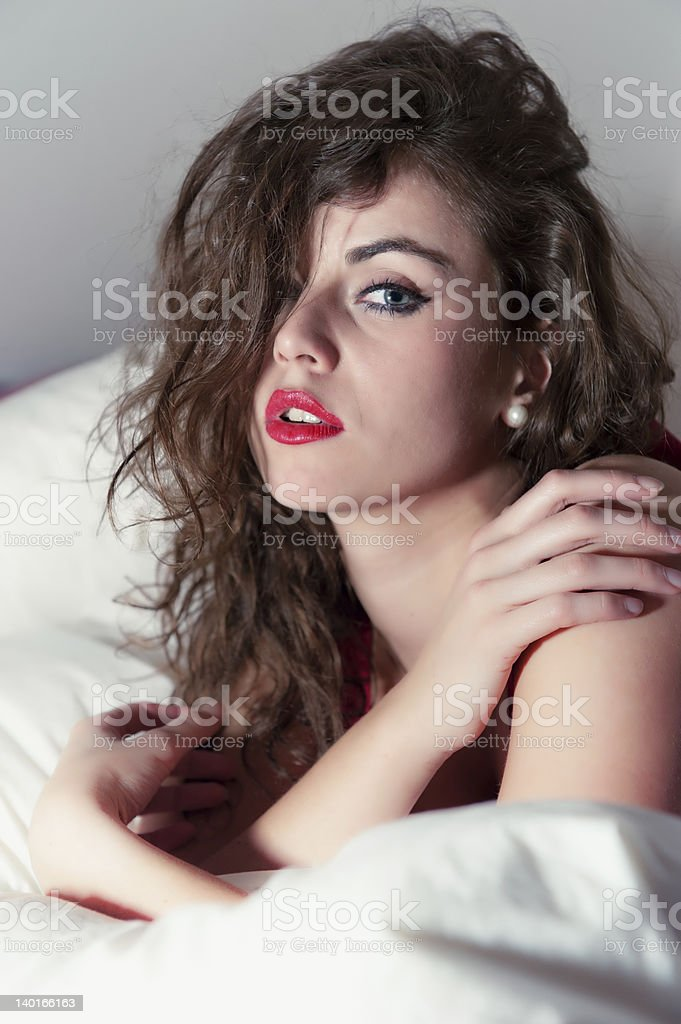 young woman with dark brown hair in bed stock photo