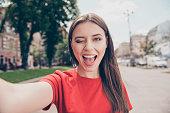 若い女性黒髪ウィンクと広い selfie をスマート フォンのカメラを正面に撮影口が開く