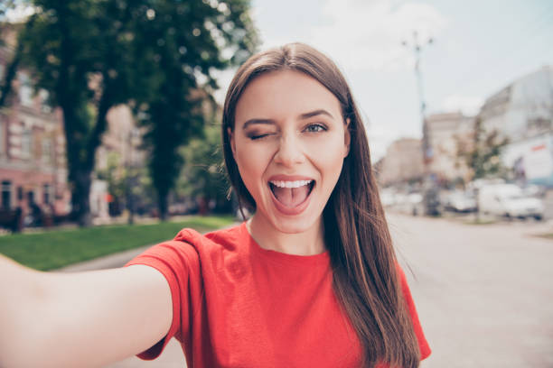 黑頭髮的年輕婦女眨眨眼和廣泛打開她的嘴射擊自拍在智慧手機前攝像頭 - 少女 個照片及圖片檔