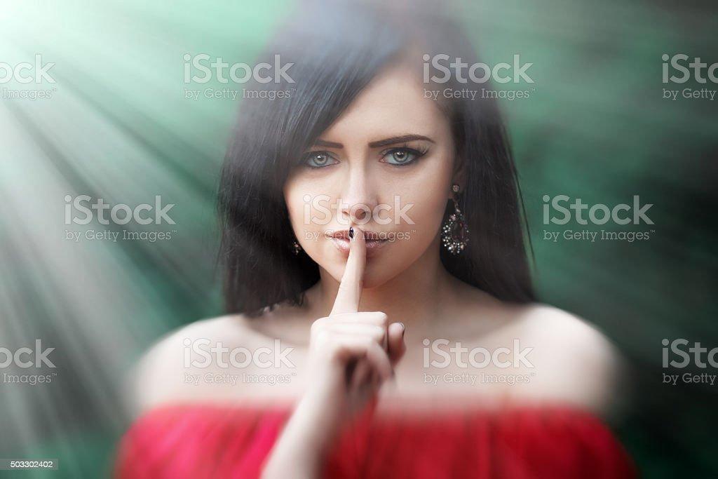 Mujer joven con largo cabello oscuro diciendo shh - foto de stock
