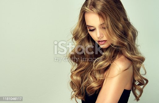 Young, woman with deep blonde,voluminous and frizzy hair..Beautiful model with long, dense, curly hairstyle and vivid makeup. Perfect dense, wavy,and shiny hair. Hairdressing art, hair care and beauty products.
