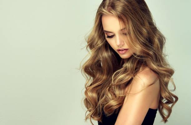 joven, mujer con pelo rubio profundo, voluminoso y encrespado. excelentes ondas capilares. peluquería, arte y cuidado del cabello. - moda de maquillaje fotografías e imágenes de stock