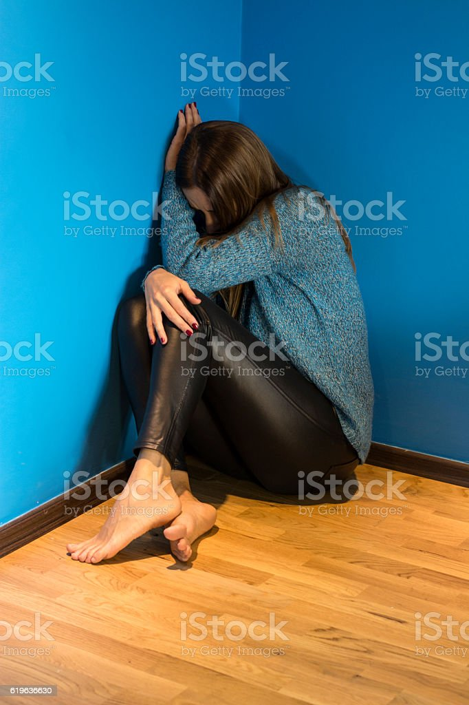 Young woman with depression sitting alone in dark room stock photo