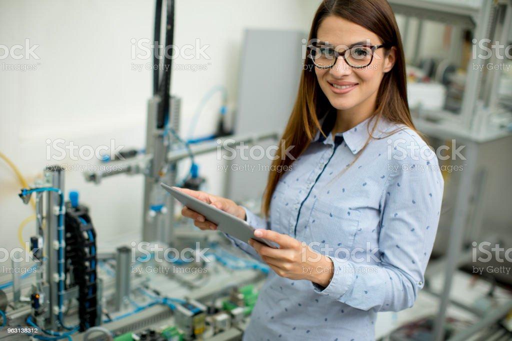 Ung kvinna med digital tablett i elektronik verkstaden - Royaltyfri Använda surfplatta Bildbanksbilder