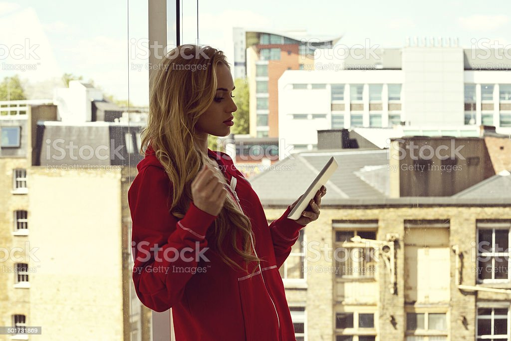 Young woman with digital tablet Young woman standing in front of window at home and reading e-book, buildings in the background. 20-24 Years Stock Photo