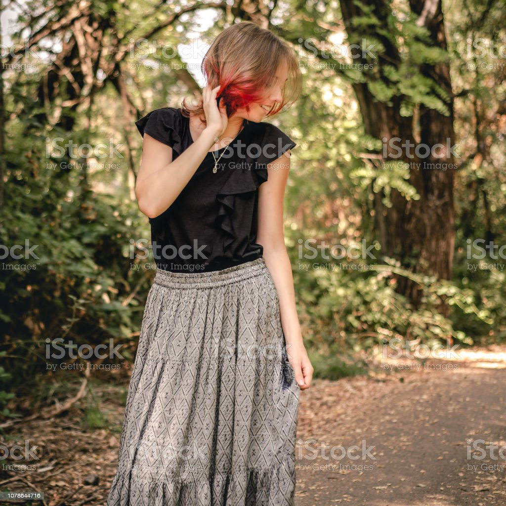 Young woman with dip-dyed red hair stands on a path outdoors stock photo